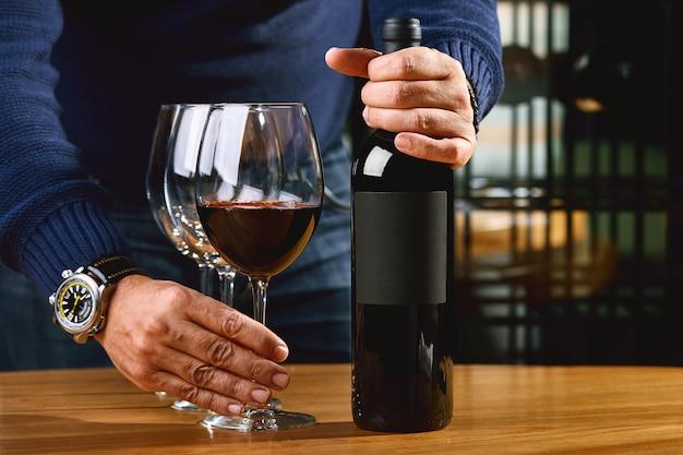 Samelie offre il vino, le mani di un enologo con un bicchiere di vino e una bottiglia stappata