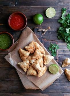 Samosa - pasticceria fritta / al forno con ripieno, popolari snack indiani, serviti in una ciotola con spezie e coriandolo fresco su fondo rustico