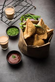 Samosa - pasta fritta / al forno a forma di triangolo con ripieno salato, famosi snack indiani dell'ora del tè, serviti con chutney verde, ketchup di pomodoro