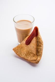 Samosa - pasta fritta / al forno a forma di triangolo con ripieno salato, famosi snack indiani dell'ora del tè, serviti con chutney verde, ketchup