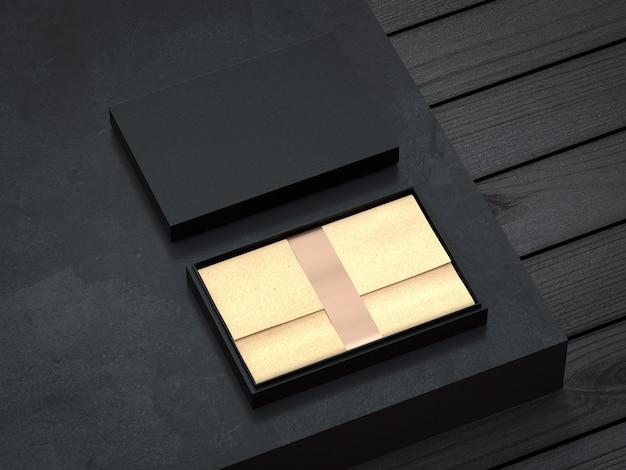 Esempio di scatola regalo in cartone nero mockup con carta kraft da imballaggio e nastro dorato