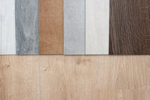 Esempio di catalogo di lussuose piastrelle per pavimenti in vinile con un nuovo design d'interni per una casa o un pavimento su un tavolo di legno chiaro.