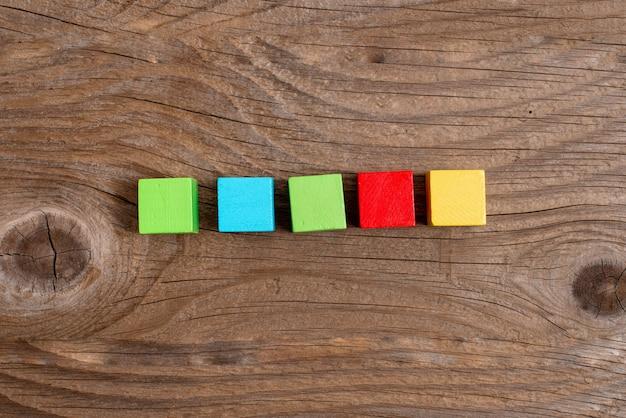 Scatole rettangolari a cubo campione lucidate con più colori che simboleggiano la stabilità lo sviluppo della crescita allineate sulla superficie con prospettive diverse delimitate da accessori per forniture elettroniche