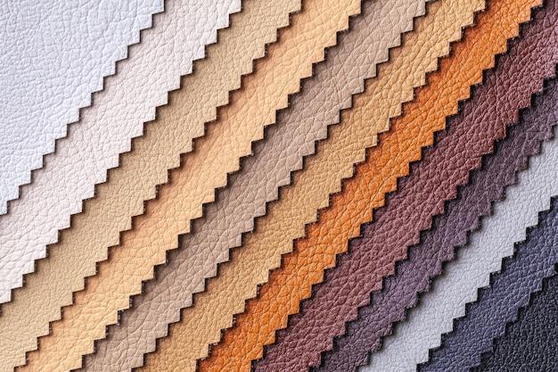Campione di colori tessili in pelle marrone e grigio, sfondo. catalogo e tonalità di tavolozza di tessuto per interni per mobili, primo piano.