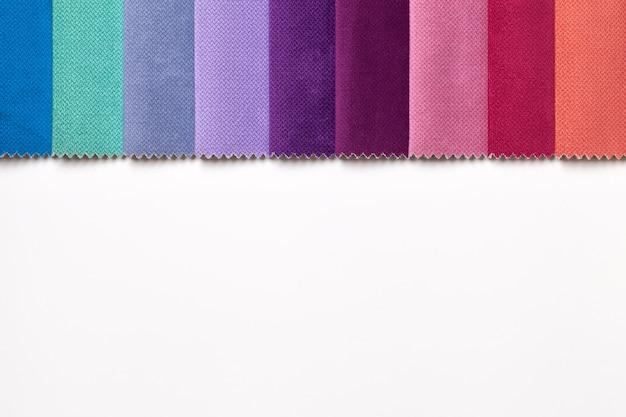 Campione di vari colori tessili di velluto, sfondo sul tavolo bianco con spazio di copia. catalogo e tonalità di tavolozza di tessuto per interni per mobili, primo piano. collezione di stoffa multicolore.