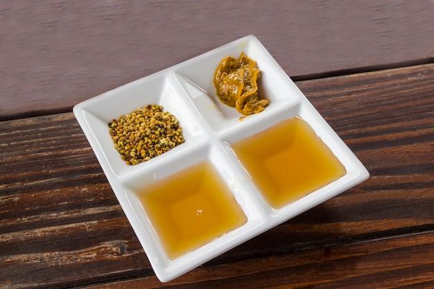Campioni di prodotti dell'apicoltura in un piatto bianco: miele, polline e miele misto con polline