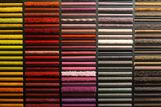 Campioni di tappeti di diversi colori su uno stand in un negozio o in una produzione. campioni di moquette multicolore sul pavimento
