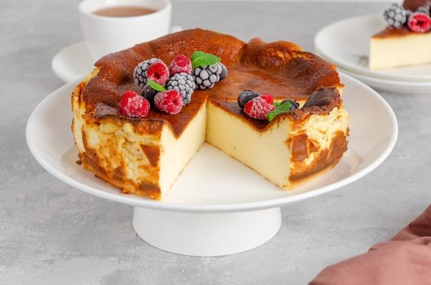 Cheesecake san sebastian con frutti di bosco e foglie di menta su un piatto alto bianco