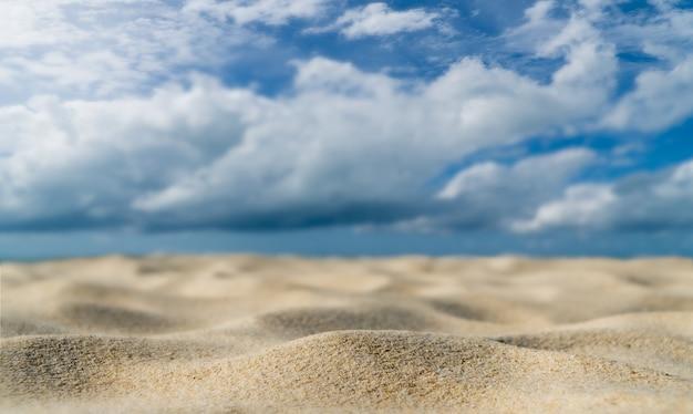 Spiaggia di sabbia al mare su sfondo di luce diurna e nuvole bianche del cielo blu