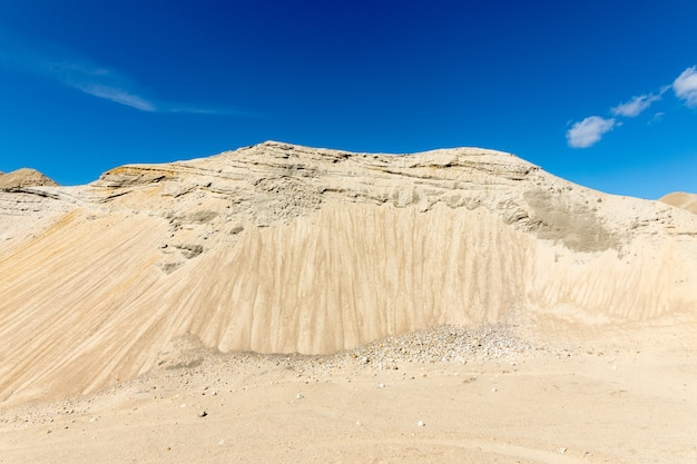 Sabbia in una grande fossa di sabbia, con cielo blu e nuvole bianche, la collina sembra una montagna