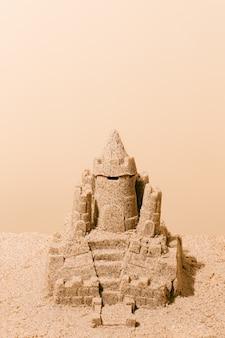 Castello di sabbia su sfondo marrone. concetto di vacanze