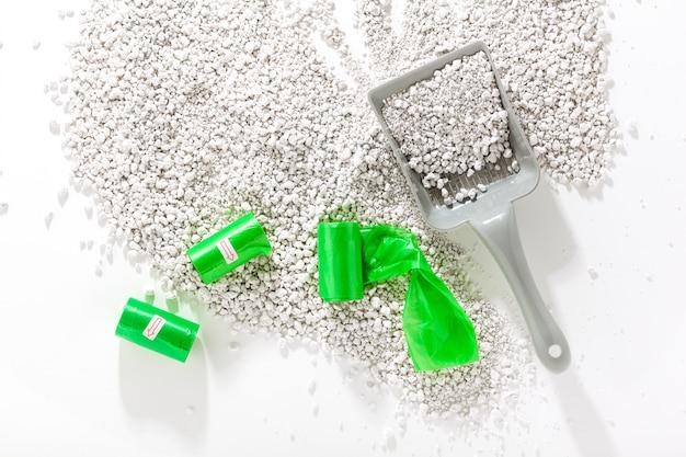 Sabbia per gatti e paletta per la pulizia. su uno sfondo bianco