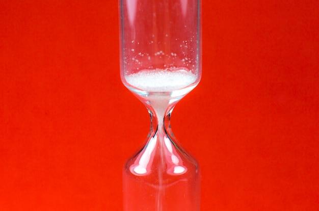 Orologio di sabbia su sfondo rosso. clessidra come concetto di tempo che passa. foto ravvicinata.