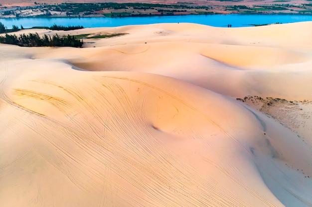 Dune di sabbia a mui ne, vietnam. bellissimo paesaggio sabbioso del deserto. dune di sabbia sullo sfondo del fiume. alba tra le dune di sabbia del mui ne.