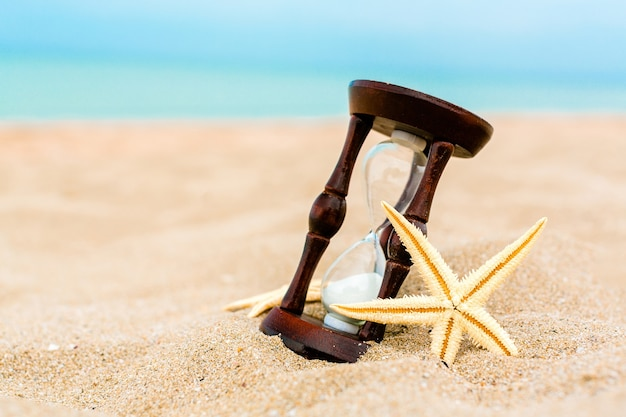 Sabbia che attraversa i bulbi di una clessidra sulla spiaggia con le stelle marine