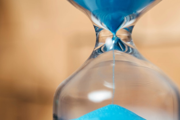 Sabbia che scorre tra i bulbi di una clessidra misurando il tempo che passa in un conto alla rovescia fino a...