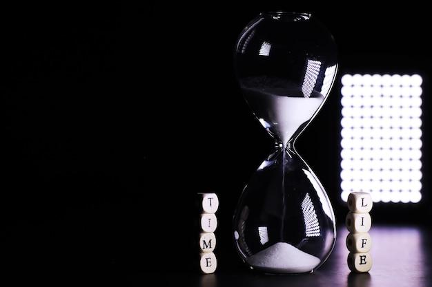 Sabbia che attraversa i bulbi di una clessidra che misura il tempo che passa in un conto alla rovescia fino a una scadenza, su uno sfondo scuro del tavolo con spazio per le copie.