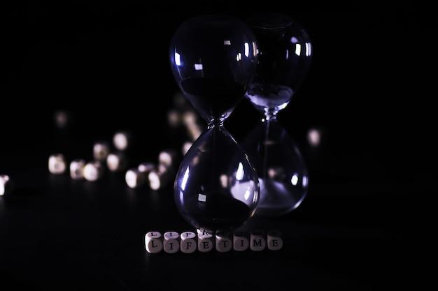 Sabbia che scorre tra i bulbi di una clessidra misurando il tempo che passa in un conto alla rovescia