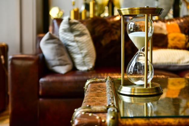 Sabbia che attraversa i bulbi di una clessidra misurando il tempo che passa nel soggiorno. accessori per la decorazione domestica
