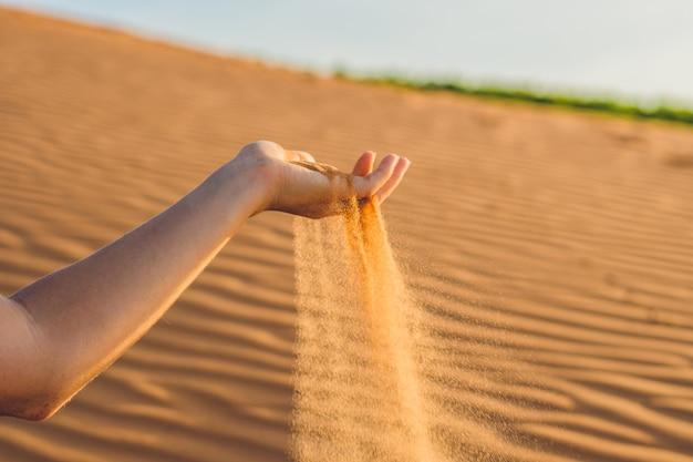 La sabbia che scivola tra le dita della mano di una donna nel deserto.