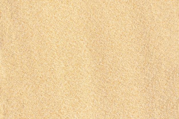 Fondo di struttura della sabbia. modello del deserto marrone dalla spiaggia tropicale. avvicinamento.