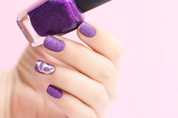 Manicure con texture sabbia. la donna mostra le unghie, tenendo la lacca per unghie in mano. concetto di cosmetici.
