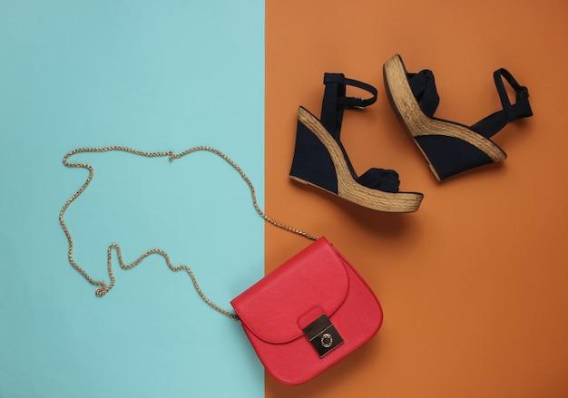 Sandali con plateau, borsa in pelle rossa su parete colorata