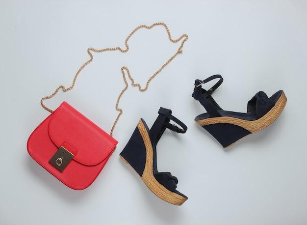 Sandali con piattaforma, borsa in pelle rossa su fondo bianco