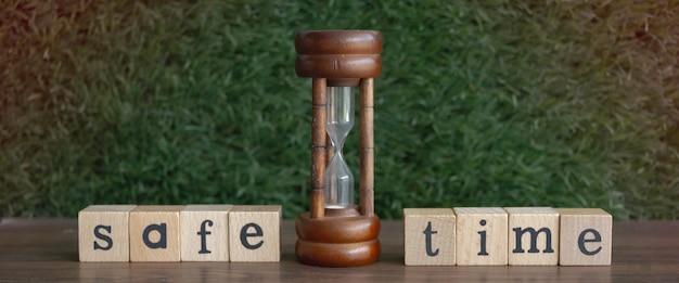 Sandclock messo al centro della parola safe time scritta sul blocco di legno, luce sfocata intorno