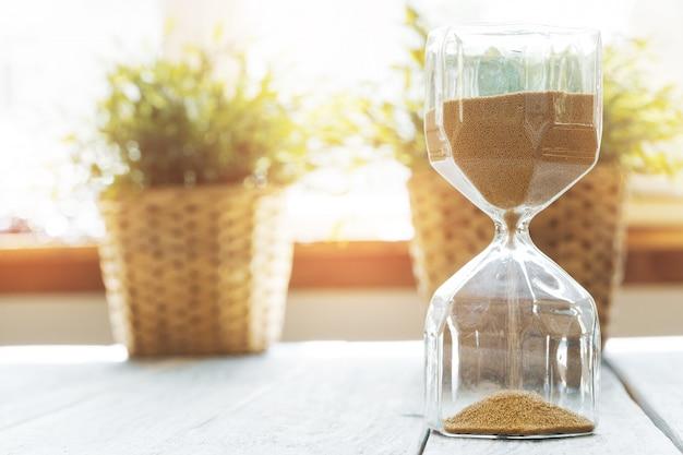 Sandglass sulla fine di legno del bakground in su. concetto di tempo