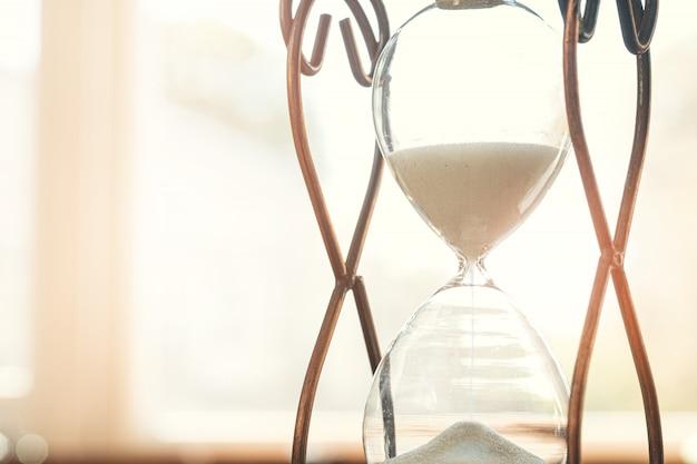 Sandglass su bakground di legno. concetto di tempo