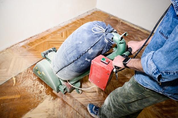 Levigatura di pavimenti in legno con la rettificatrice. riparazione nell'appartamento.