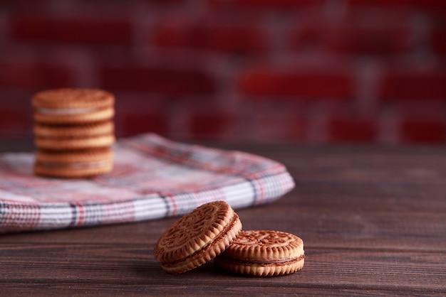 Biscotti sandwich, biscotti alla crema, biscotti con ripieno di crema su tavola di legno