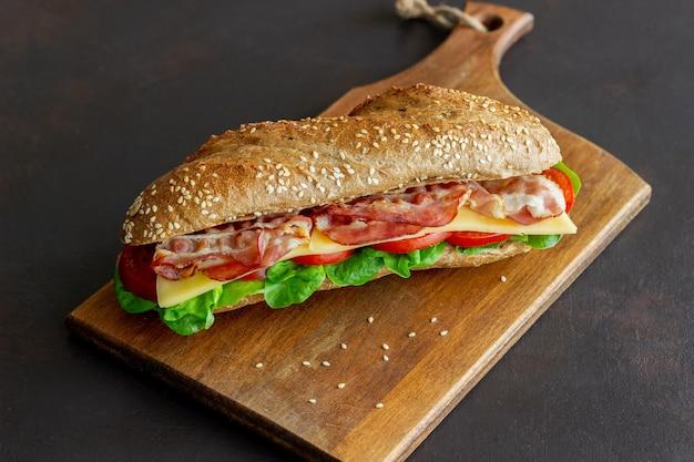 Un panino di pane scuro con insalata, pancetta, pomodori e formaggio. colazione. fast food.