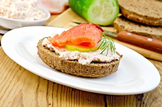 Panino di pane di segale con panna, cetriolo, aneto e salmone su un piatto ovale su uno sfondo di assi di legno