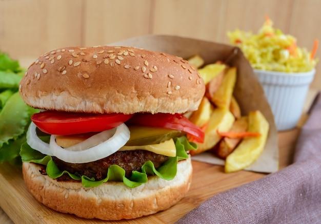 Panini morbidi, formaggio, pomodori e hamburger succosi. insalata di cavolo. patatine fritte. fast food.