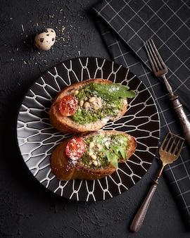 Panino in padella con pesto fatto in casa, basilico, olio d'oliva, aglio e anacardi. tabella di sfondo. concetto di foto di cibo helthy. sfondo nero scuro
