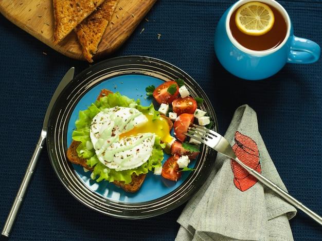 Panino, uovo in camicia e insalata su uno sfondo scuro