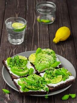 Sandwich su pane di segale con avocado, formaggio, microgreens, semi di sesamo e punte di abete rosso in una piastra su un tavolo di legno scuro