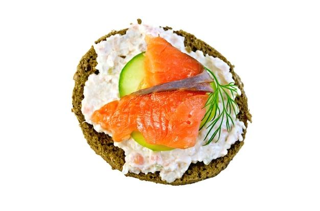 Panino di pane di segale con panna, cetriolo, aneto e salmone isolato su sfondo bianco dall'alto