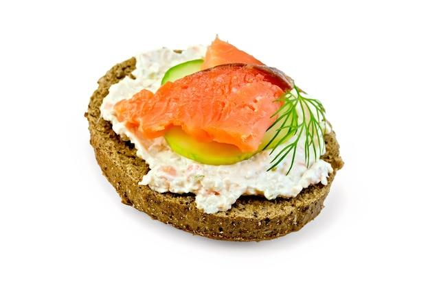 Panino di pane di segale con panna, cetriolo, aneto e salmone isolato su sfondo bianco