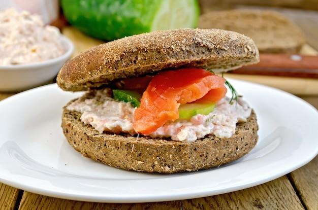 Panino di pane di segale con panna, cetriolo, aneto e salmone su un piatto su uno sfondo di assi di legno