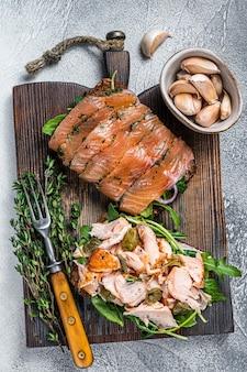 Sandwich toast con salmone affumicato caldo e freddo, rucola e crema di formaggio su una tavola di legno. sfondo bianco. vista dall'alto.