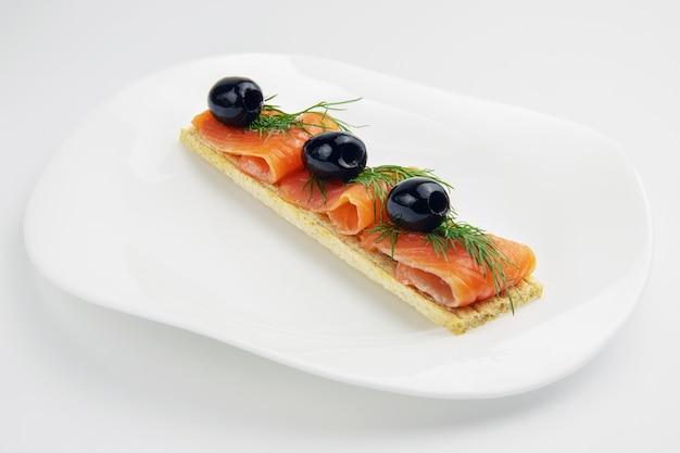 Panino o pane tostato con fette di trota rossa pesce e rametto di aneto nella piastra bianca su sfondo bianco, dieta alimentare per il fitness