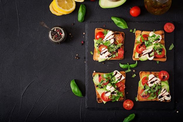 Pane tostato con pomodoro, mozzarella, avocado e basilico con aceto balsamico.