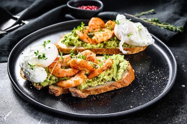 Sandwich condito con gamberi freschi, gamberetti su avocado con uovo. un cibo sano, cucina scandinava