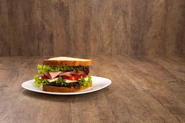 Panino su un piatto bianco con petto di tacchino, pomodoro, lattuga e formaggio sul tavolo