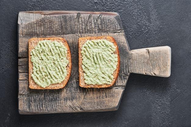 Panino di pane integrale e guacamole su una vecchia tavola di legno.