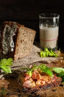 Panino con pancetta e foglie di sedano su una fetta di pane di segale lievitato con semi di zucca