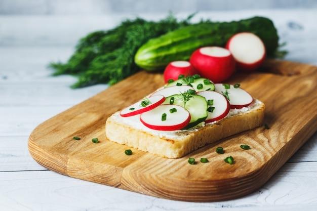 Panino con formaggio cremoso ravanello cetriolo e cipolle verdi su tagliere su fondo di legno grigio